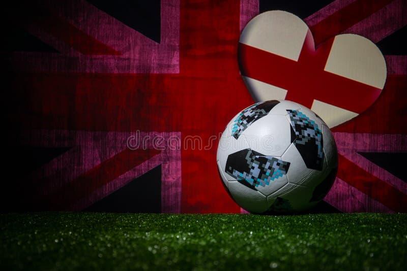 BAKU,AZERBAIJAN - JULY 08, 2018 : Creative concept. Official Russia 2018 World Cup football ball The Adidas Telstar 18 on green gr. Ass. Support England team stock image