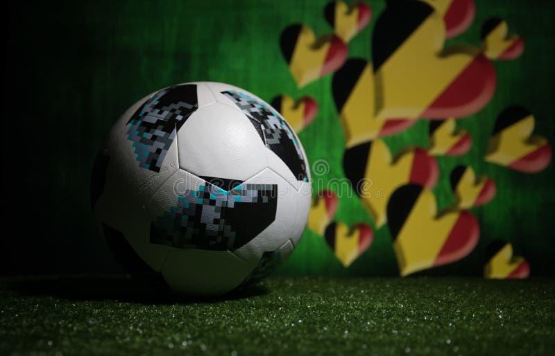 BAKU,AZERBAIJAN - JULY 08, 2018 : Creative concept. Official Russia 2018 World Cup football ball The Adidas Telstar 18 on green gr. Ass. Support Belgium team stock photo