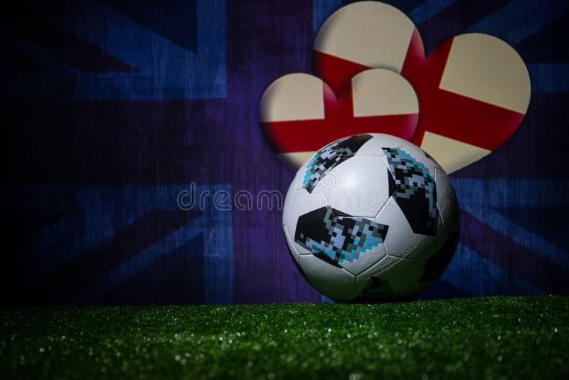 BAKU,AZERBAIJAN - JULY 08, 2018 : Creative concept. Official Russia 2018 World Cup football ball The Adidas Telstar 18 on green gr. Ass. Support England team royalty free stock images