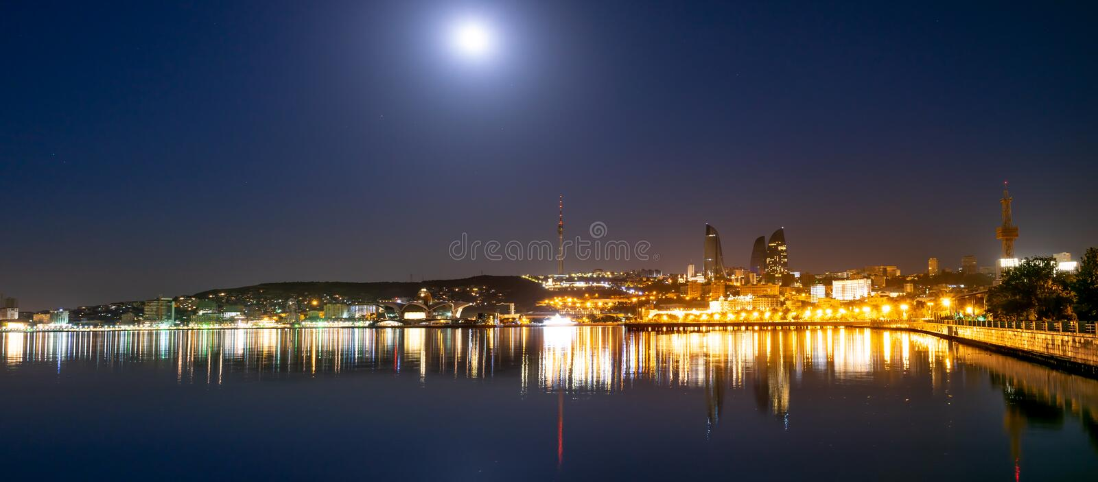 Baku Azerbaijan - 16 June, 2019. Reflection of the lights of the night city in the caspian sea. Night view of Baku with the Flame royalty free stock images