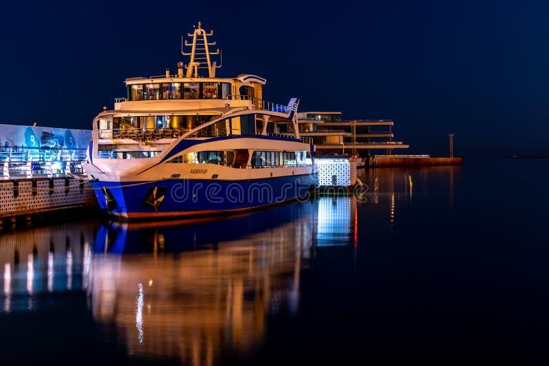 Baku Azerbaijan - 16 Juni, 2019 Modern kryssningeyeliner i hamnen på natten Kaspiska hav tillsammans med Baku Boulevard royaltyfri fotografi