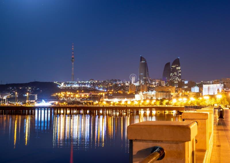 Baku Azerbaijan - 16. Juni 2019 Reflexion der Lichter der Nachtstadt im Kaspischen Meer Nachtansicht von Baku mit der Flamme lizenzfreie stockfotografie