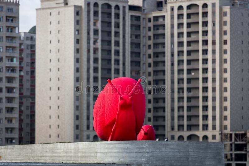 Baku, Azerbaijan, Novemver 07.2016: Giant sculpture of a red snail. Close-up in a park near the center of Heydar Aliyev on the background of city buildings stock images