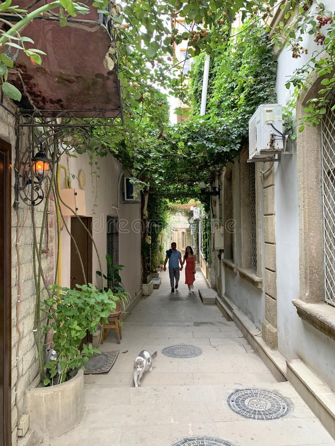 Baku, Azerbaijan, September, 09, 2019. People and cat walking down  narrow alley in the old town of Icheri Sheher in autumn in Bak royalty free stock image