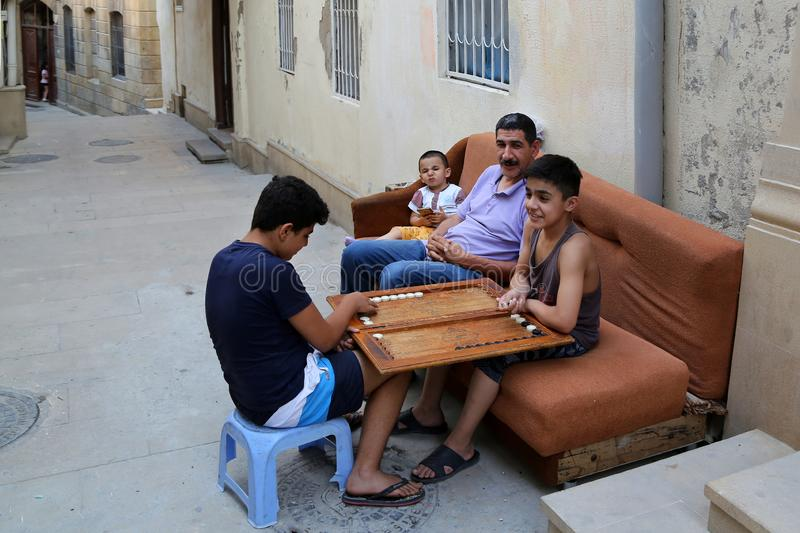 Residents of the old city of Icheri Sheher playing backgammon on the street stock photography