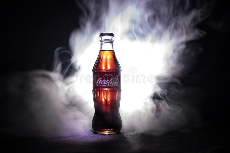Baku, Azerbaijan 13th January 2018, Coca-Cola Classic in a glass bottle on dark toned foggy Background. Coca Cola is the most popu royalty free stock images