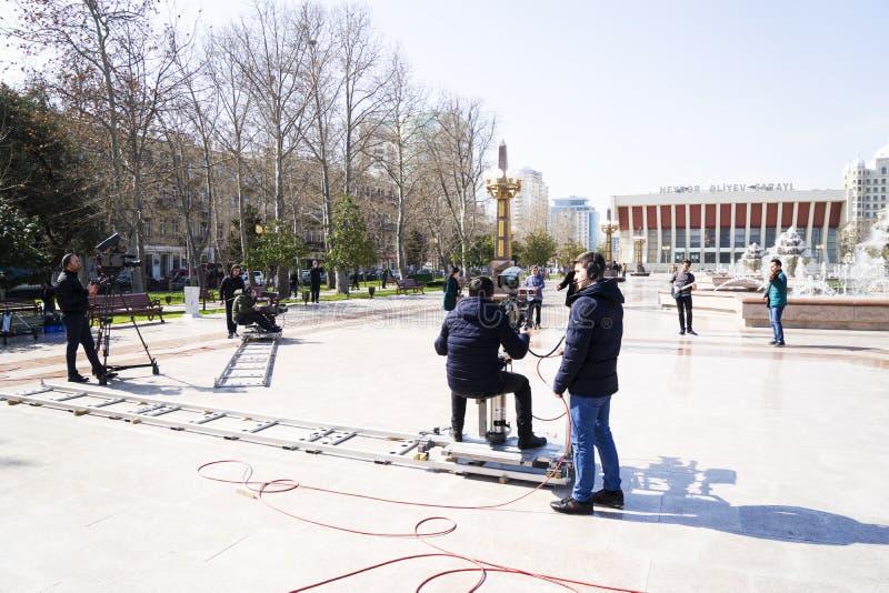 Baku, Azerbayjan, 10 puede, 201: Cameraman que tira un concierto vivo en parque de la ciudad foto de archivo