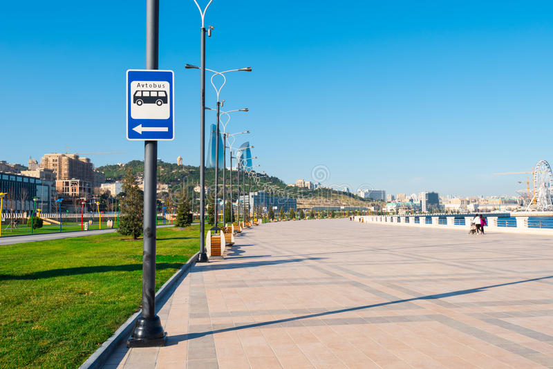 Baku bay embankment. Warning road sign on the pole, bus stop. Baku city, Azerbaijan. National seaside park stock photography