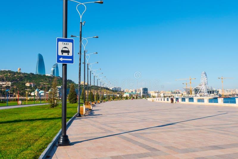 Baku bay embankment. Warning road sign on pole, taxi stop. Baku city, Azerbaijan. National seaside park royalty free stock photography