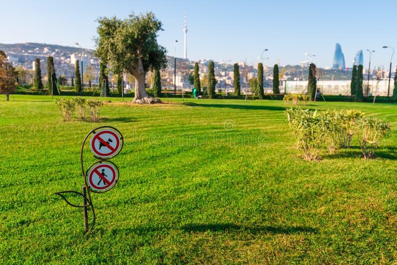 Baku bay embankment. Warning sign on the lawn. Baku city, Azerbaijan. National seaside park stock images