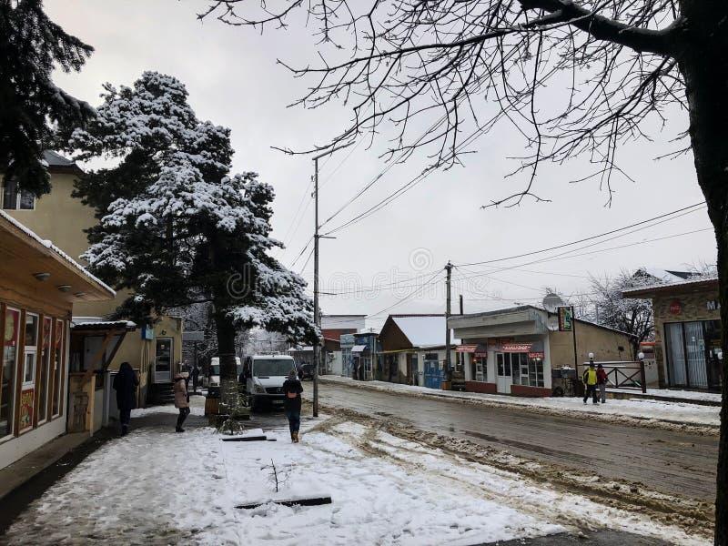 BAKURIANI, ΓΕΩΡΓΙΑ - 17 ΝΟΕΜΒΡΊΟΥ 2018: Χειμερινό μεσημέρι Οι άνθρωποι περπατούν στο χιόνι Χιονώδης οδός Χιονοδρομικό κέντρο Baku στοκ εικόνες με δικαίωμα ελεύθερης χρήσης