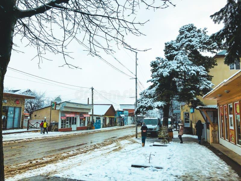 BAKURIANI, ГРУЗИЯ - 17-ОЕ НОЯБРЯ 2018: Полдень зимы Люди идут в снег Улица Snowy Лыжный курорт Bakuriani горы стоковое фото rf