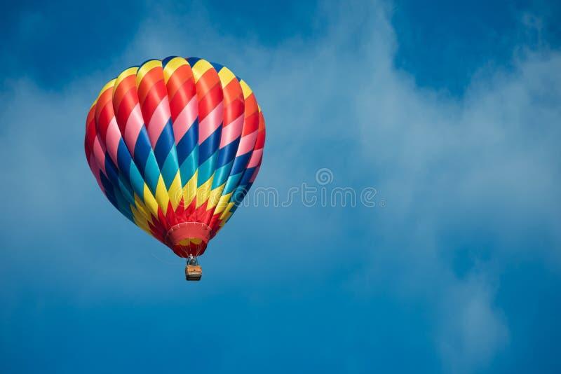 Balão de ar quente brilhantemente colorido com um fundo dos azul-céu imagem de stock royalty free