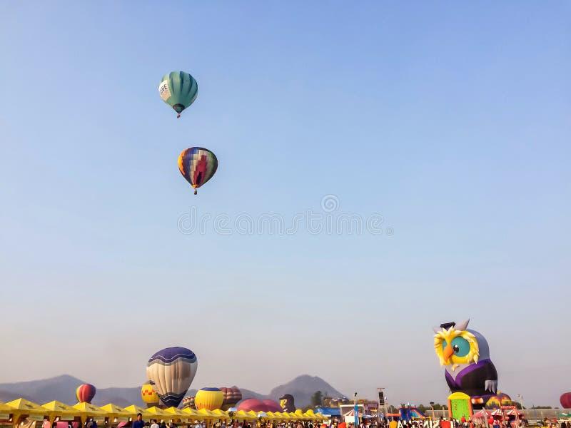 Balão de ar quente colorido que flutua sobre o prado com montanha e o céu azul no parque Chiang Rai International Balloon Fiesta  imagens de stock royalty free