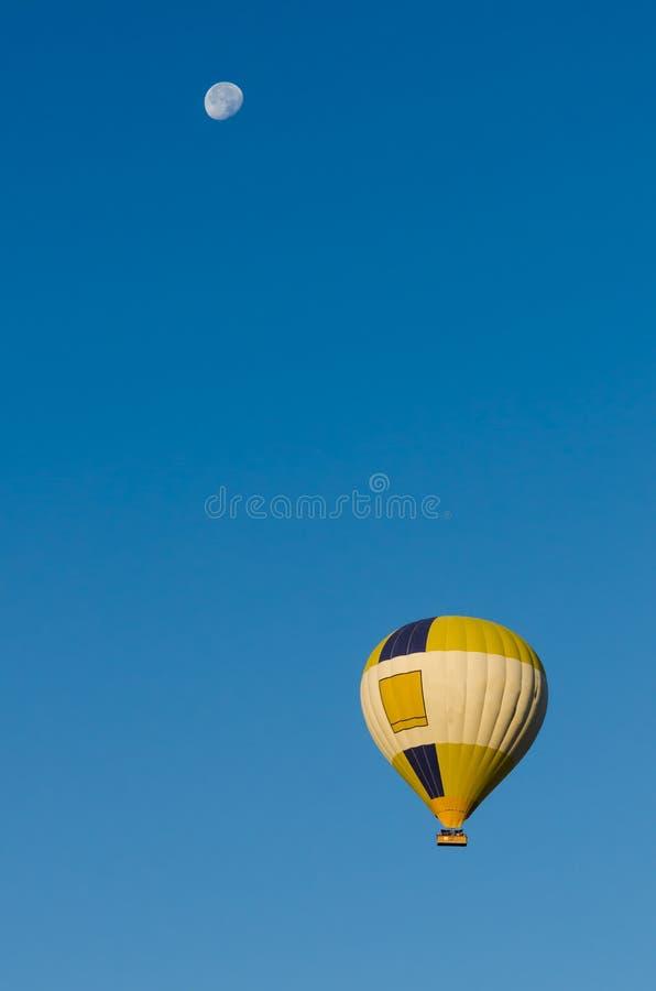 Balão de ar quente que voa sobre o céu azul claro com lua foto de stock