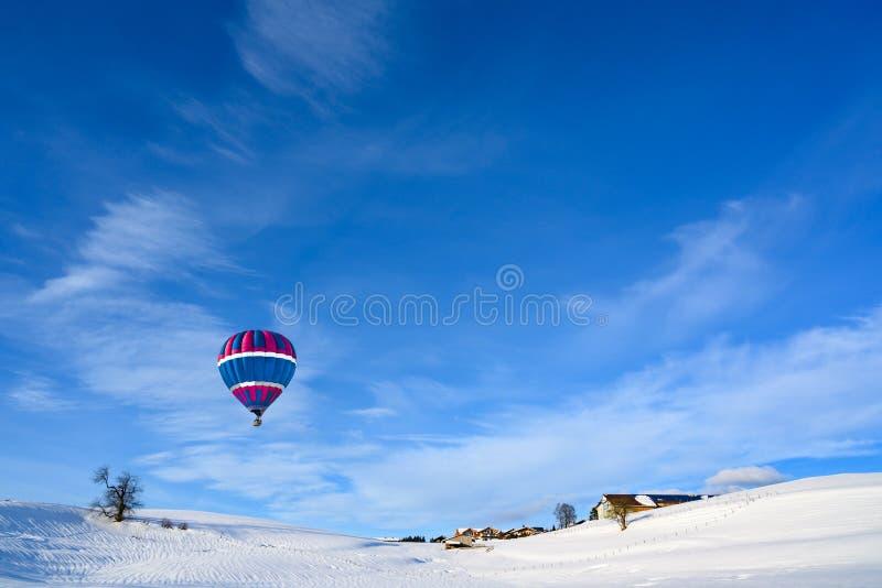 Balão de ar quente sobre a paisagem coberto de neve e a vila rural pequena, Baviera, Alemanha imagens de stock royalty free