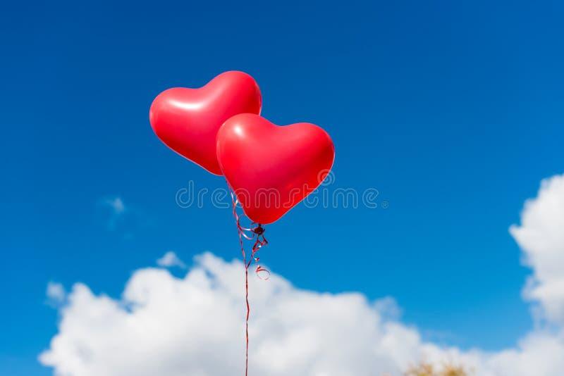 Balão do coração do Valentim de encontro ao fundo do céu azul foto de stock