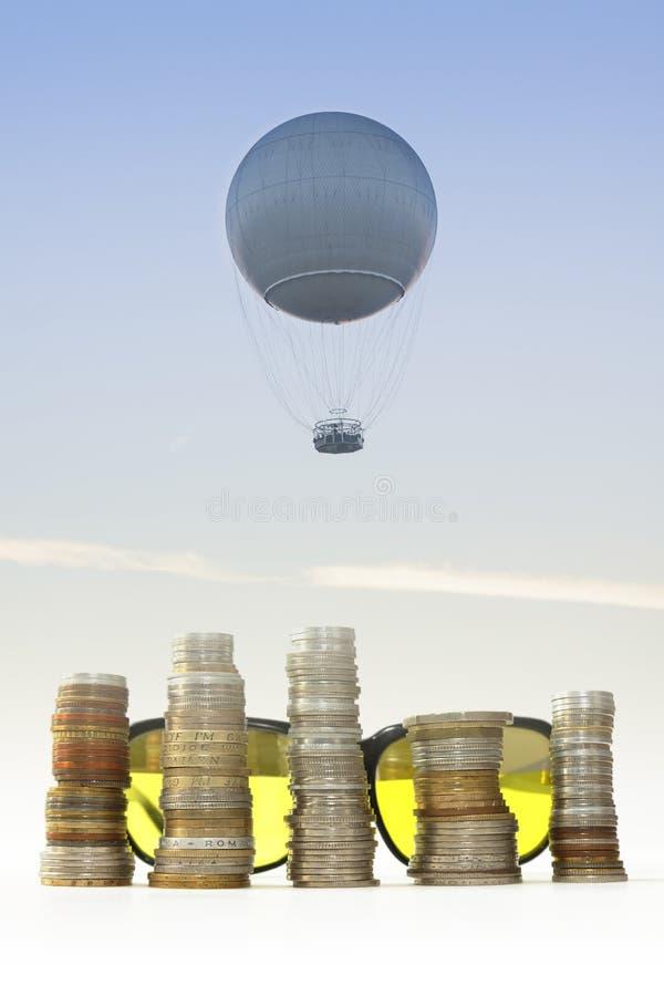 Balão do gás, estacas das moedas e óculos de sol contra o céu imagens de stock