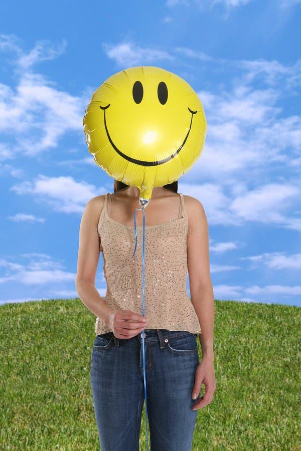 Balão do smiley da terra arrendada da mulher imagem de stock