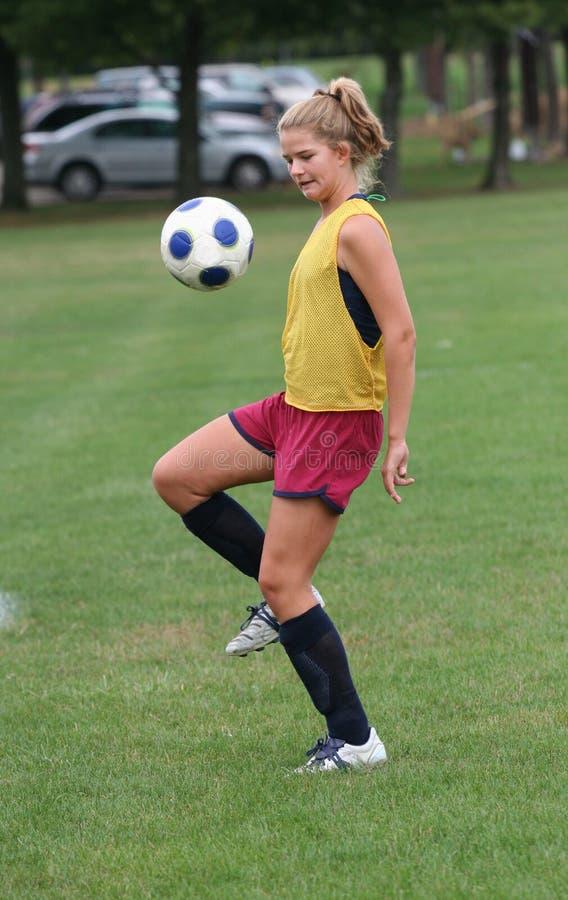 Balón de fútbol adolescente de Boucing de la juventud en aire imagenes de archivo