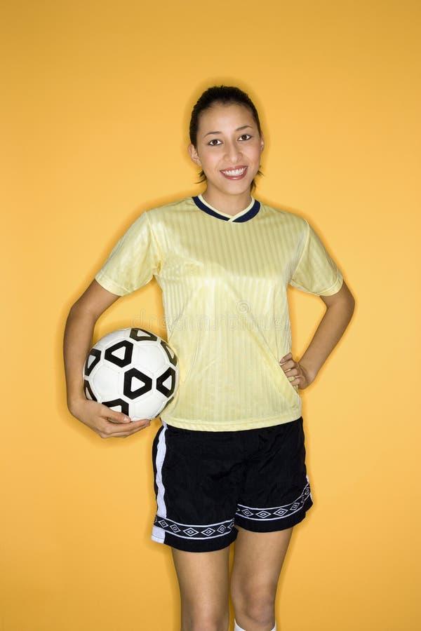 Balón de fútbol adolescente multirracial de la explotación agrícola de la muchacha. fotografía de archivo libre de regalías