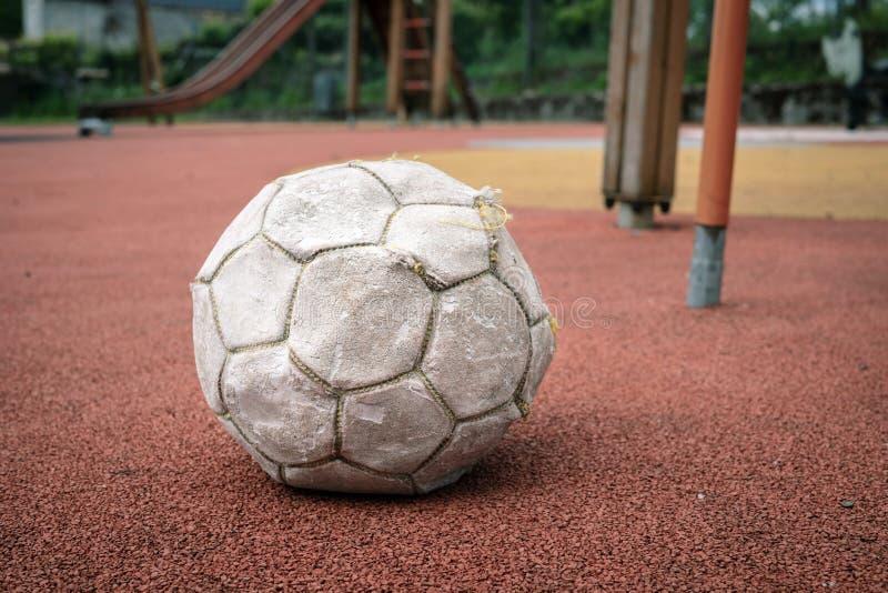 Balón de fútbol blanco dañado en patio imágenes de archivo libres de regalías