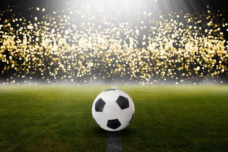 Balón de fútbol clásico en el campo con las luces borrosas fotos de archivo libres de regalías