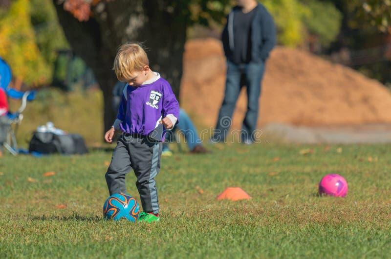 Balón de fútbol de goteo del muchacho joven fotos de archivo libres de regalías