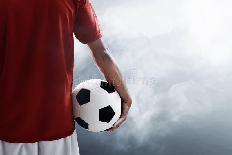 Balón de fútbol del control del jugador de fútbol fotografía de archivo libre de regalías