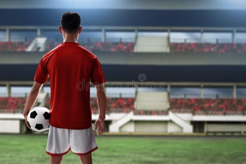Balón de fútbol del control del jugador de fútbol imagenes de archivo