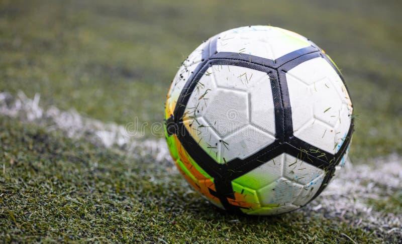 Balón de fútbol del fútbol en la línea del campo con la hierba en ella, aislada, con el espacio de la copia, el papel pintado, fo fotografía de archivo