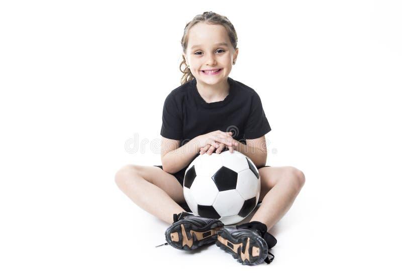 Balón de fútbol del juego de la chica joven, aislado sobre blanco fotografía de archivo