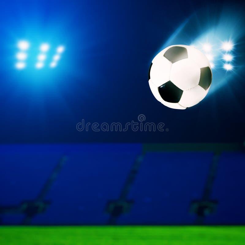 Balón de fútbol del vuelo sobre campo verde fotos de archivo libres de regalías