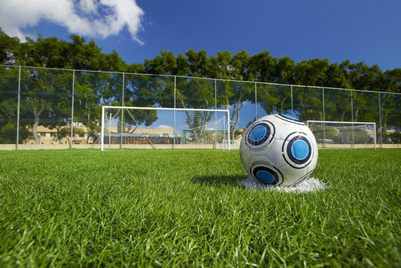 Balón de fútbol en campo de fútbol imagenes de archivo