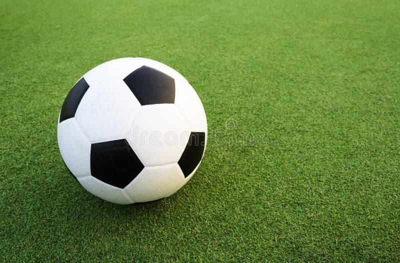 Balón de fútbol en campo verde fotos de archivo