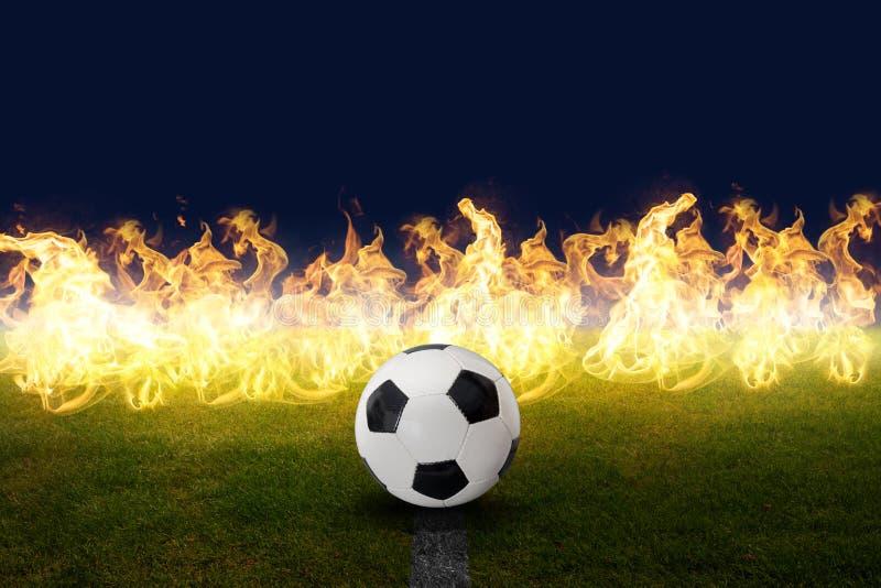 Balón de fútbol en el césped del estadio con efecto de fuego fotografía de archivo