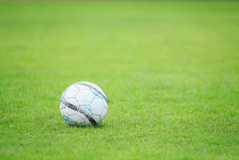 Balón de fútbol en el campo y la falta de definición del jugador en estadio imagenes de archivo
