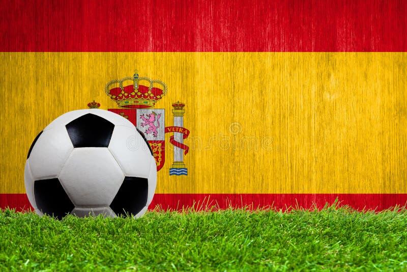 Balón de fútbol en hierba con el fondo de la bandera de España imagenes de archivo