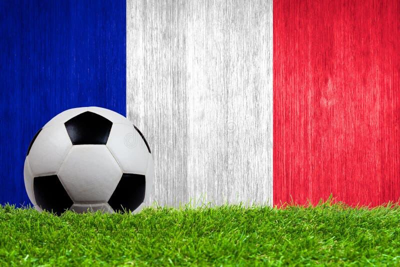 Balón de fútbol en hierba con el fondo de la bandera de Francia foto de archivo