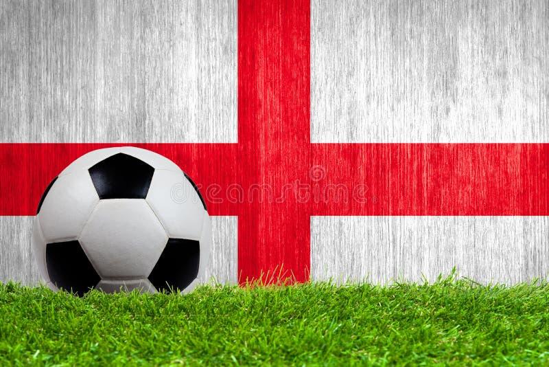 Balón de fútbol en hierba con el fondo de la bandera de Inglaterra imagen de archivo