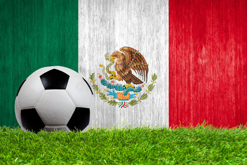 Balón de fútbol en hierba con el fondo de la bandera de México fotos de archivo libres de regalías