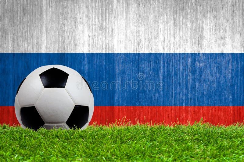 Balón de fútbol en hierba con el fondo de la bandera de Rusia imágenes de archivo libres de regalías