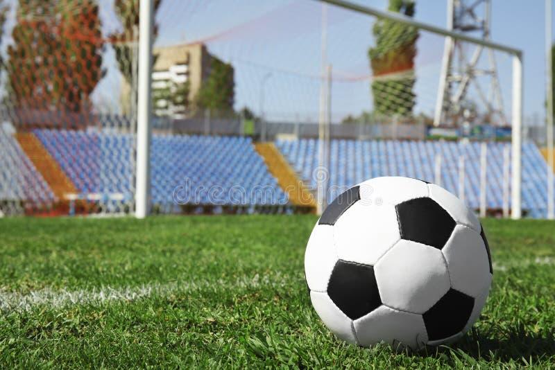 Balón de fútbol en hierba verde del campo de fútbol contra red imagen de archivo libre de regalías
