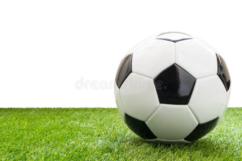 Balón de fútbol en la hierba artificial aislada en el fondo blanco imagen de archivo