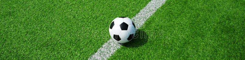 Balón de fútbol en la hierba artificial verde, formato de paisaje, para una bandera fotografía de archivo libre de regalías