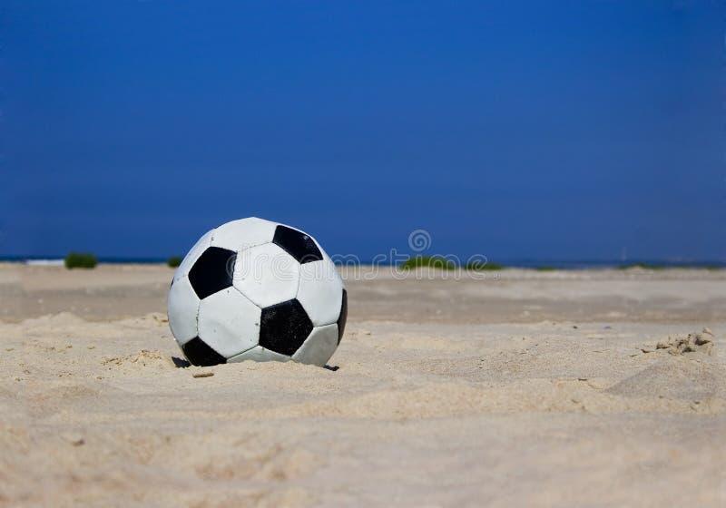Balón de fútbol en la playa arenosa fotografía de archivo