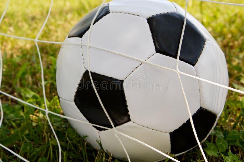 Balón de fútbol en la red de la meta fotografía de archivo