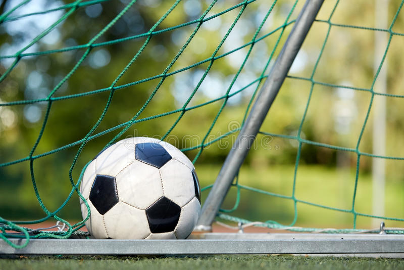 Balón de fútbol en la red de la meta en campo de fútbol fotografía de archivo