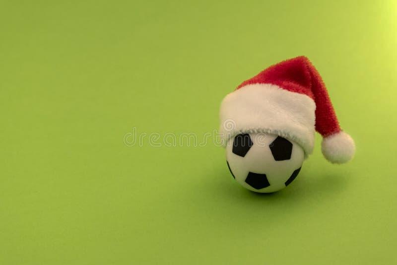 Balón de fútbol en un sombrero rojo de Santa Claus Fondo verde Copie el espacio El concepto del regalo del Año Nuevo de los depor foto de archivo libre de regalías