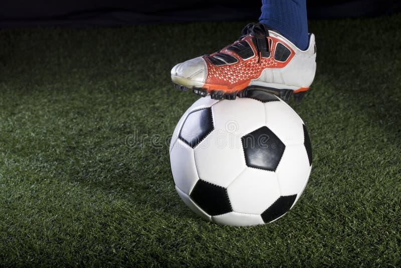 Balón de fútbol que se reclina sobre un campo de hierba en la noche imagen de archivo